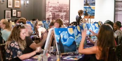 Artist leading PopUp Painting event, painting is Van Gogh's Starry Night